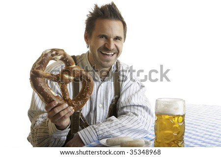 Bavarian Man is sitting on bench and holding in his hand an Oktoberfest Pretzel. Beside him is a full Beer Stein (Mass). - stock photo