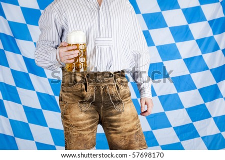 Bavarian man with leather pants (Lederhose) holds Oktoberfest beer stein (Mass) . In background is Bavarian flag visible. - stock photo