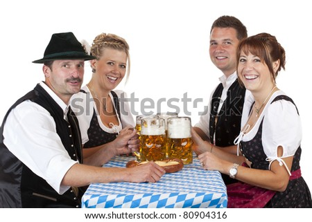 Bavarian men and women toast with Oktoberfest beer stein. Isolated on white background. - stock photo