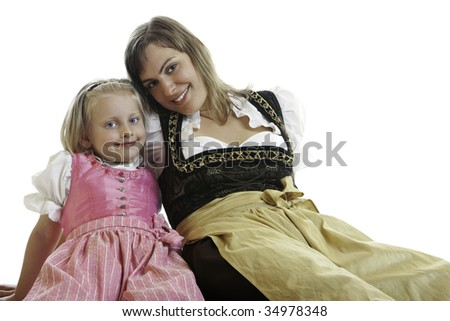 Bavarian Mother and Daughter are sitting on the floor dressed with typical Oktoberfest Dirndl - stock photo