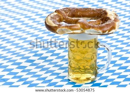Bavarian Oktoberfest pretzel is lying on beer stein (Mass). In Background is the Bavarian Flag visible. - stock photo