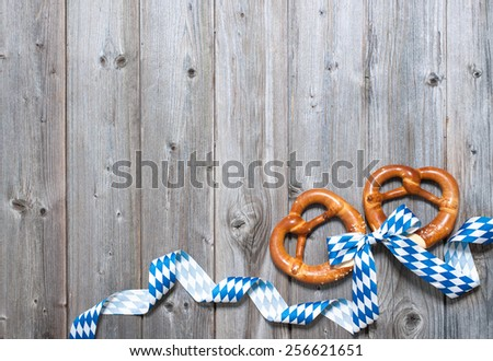 Bavarian pretzels with ribbon on wooden board as a background for Oktoberfest - stock photo
