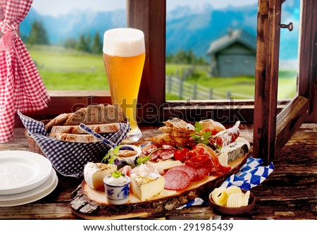 Bavarian tavern lunch with bread, assorted cold spicy sausage and meat, cheese and a long ice cold beer on a rustic wooden windowsill with a view of the Alps - stock photo
