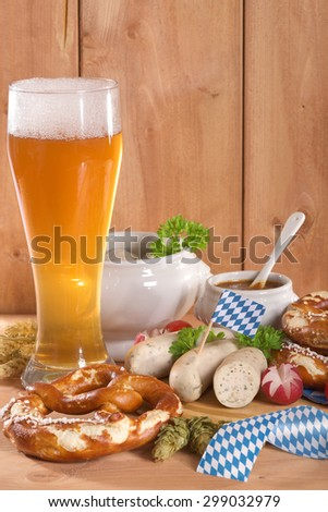 Bavarian veal sausage breakfast with sausages, soft pretzel, weissbier and mild mustard on wooden board - stock photo