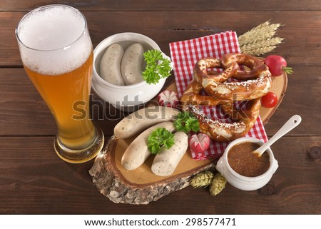 Bavarian veal sausage breakfast with sausages, weissbier, soft pretzel and mild mustard on dark weathered wooden board - stock photo