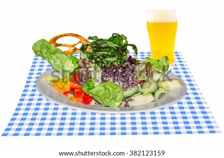 Bavarian vegetarian food from above. Salad with beer and pretzel on blue white table cloth. - stock photo
