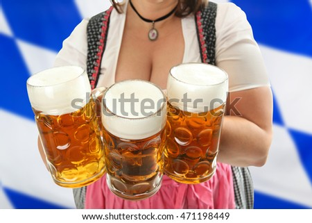 Bavarian Waitress holding Oktoberfest Beer in front of her cleavage with a bavarian flag in the background