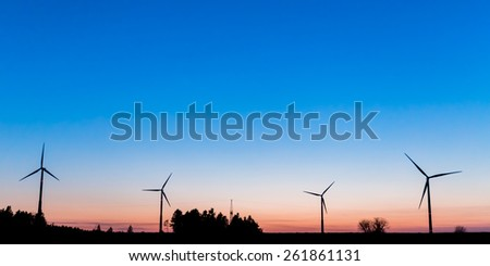Bavarian Windmills in Upper Franconia, Germany after sunset. Early March. Clear Blue Sky. Regenerative Energy. Huge Turbines. Silhouette Picture