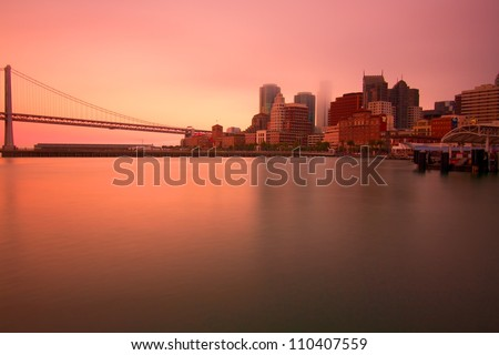 Bay Bridge and San Francisco panorama during sunset across the bay, USA - stock photo