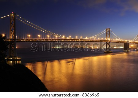 Bay Bridge, San Francisco glows in the dusk with traffic taillights leaving red ribbons across its' span.