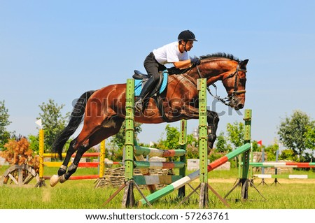 Bay horse and rider over a jump - stock photo