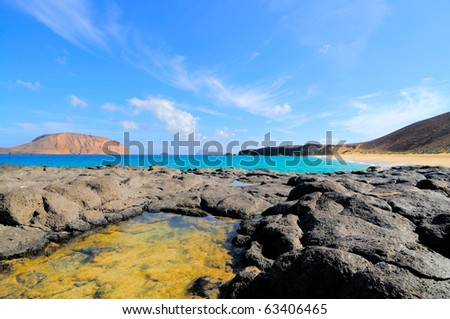 Bay Las Conchas; north of Island Graciosa, a small volcanic island North from Lazarote. A little island across the bay on the left is called Isla de Montana Clara. - stock photo