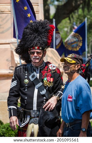 Bay Pines, Florida - May 26 : Bagpiper and navy veteran posing for a photo after the Memorial Day parade, May 26 2014 in Bay Pines VA cemetery in Florida