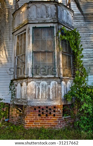 Bay wind on old dilapidated house in the shadows of the late afternoon - stock photo
