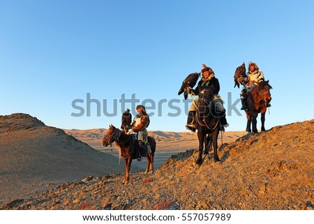 BAYAN-ULGII, MONGOLIA - SEP 26: Three senior mongolian horsemen in traditional kazakh clothing with altai golden eagle on dawn of village sagsai his on September 26, 2016 in Bayan-Ulgii, Mongolia