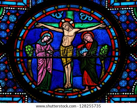 BAYEUX - FEBRUARY 12: Stained glass window depicting Jesus on the Cross in the cathedral of Bayeux, Normandy, France on February 12, 2013. - stock photo