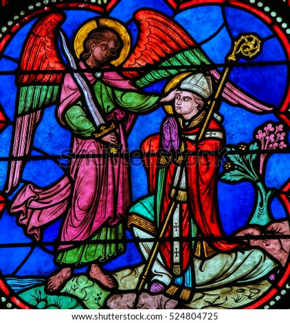 BAYEUX, FRANCE - FEBRUARY 12, 2013: Stained Glass window in the Cathedral of Bayeux, France, depicting the Archangel Michael blessing a Catholic Saint