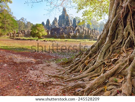 Bayon temple carving of the face with sunbeams through the rainforest  - stock photo