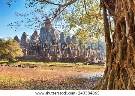 Bayon temple landscape on sunrise. Prehistoric ancient tree with roots on foreground - stock photo