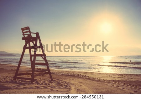 Baywatch chair in a beautiful beach empty at summer sunset. Soft and warm tones edition. - stock photo