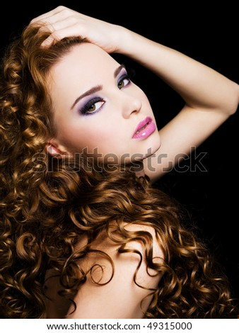 Bbeautiful  woman with beauty  long  hairs and bright pink make-up. On a black background - stock photo