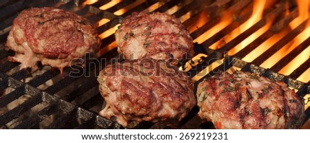 BBQ Beef Burgers on Hot Charcoal Grill. Dancing Flames On The Background - stock photo