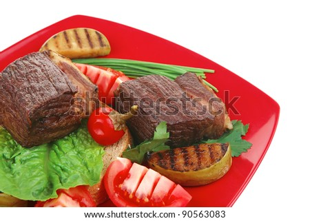 bbq : beef (pork) steak garnished with apples , fresh tomatoes, hot pepper, chives and lettuce, on bread, over red plate isolated on white background - stock photo