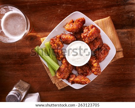 bbq buffalo chicken wings with beer ranch and celery shot top down - stock photo