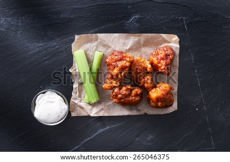 bbq chicken hot wings on parchment paper with ranch and celery - stock photo