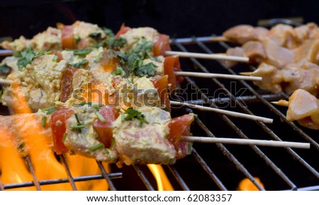 BBQ chicken kebabs on grill with flames