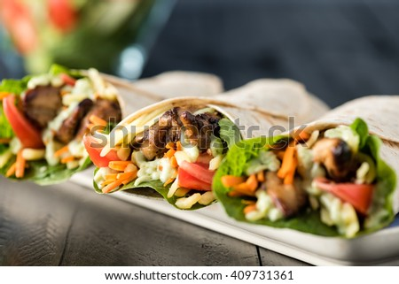 BBQ chicken with fresh salad tortilla wraps on rustic background