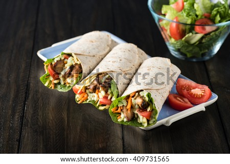 BBQ chicken with fresh salad tortilla wraps on rustic background - stock photo