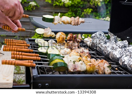 BBQ cooking. Managing the sticks on a grate. - stock photo