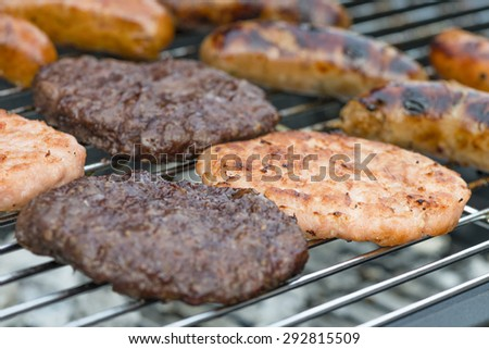 BBQ - Exotic meat burgers and sausages on a lit barbecue (kangaroo, crocodile and wild boar). - stock photo