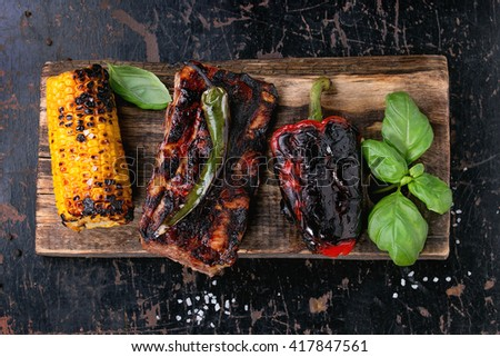 BBQ grilled pork ribs, corn, green chili and red bell pepper, served on wooden chopping board with salt and fresh basil over black wooden background. Flat lay - stock photo