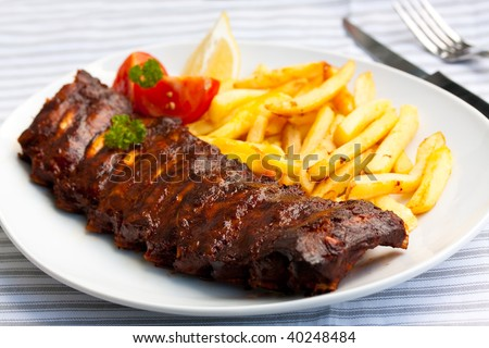 BBQ marinated spareribs and fries - stock photo