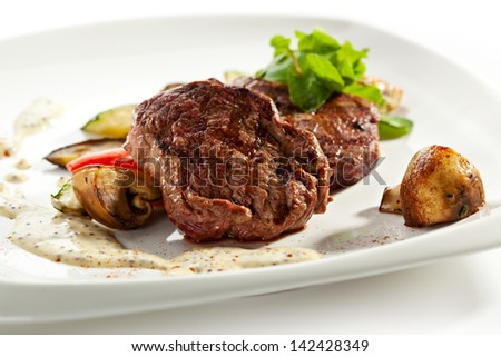 BBQ Pork with Mushrooms Sauce. Garnished with Vegetables and Mushrooms - stock photo