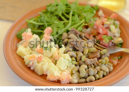 BBQ Salads - Plate with traditional Brazilian side dishes - potato salad, black eyed pea salad, tomato and onion salsa and coriander.
