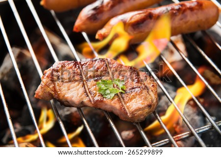 BBQ sausages and meat on the grill - stock photo