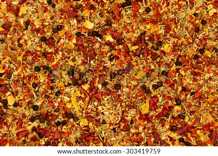 BBQ spices mix - garlic, sea salt, chili pepper,  black pepper corns, cumin, grated nutmeg, coriander, rosemary,  thyme, aniseed, chopped dried tomatoes; close up - stock photo
