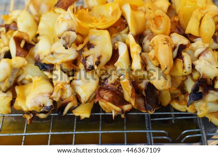 bbq squid stick they look yellow because of soy sauce as seasoning - thai street food                                - stock photo