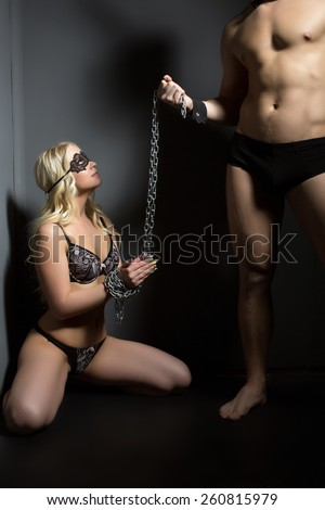 BDSM concept. Beautiful submissive tied with chain - stock photo
