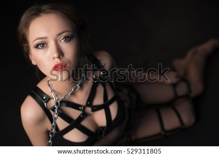 BDSM. Studio photo of beautiful girl on leash