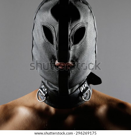Bdsm style image with a men wearing a leather mask or hood over his head - stock photo