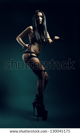 bdsm woman in black wear with whip - stock photo