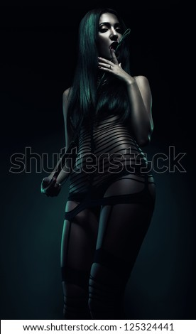bdsm woman with whip on mouth - stock photo