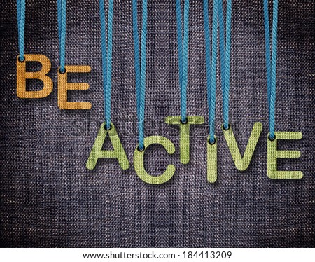 Be Active Letters hanging strings with blue sackcloth background. - stock photo