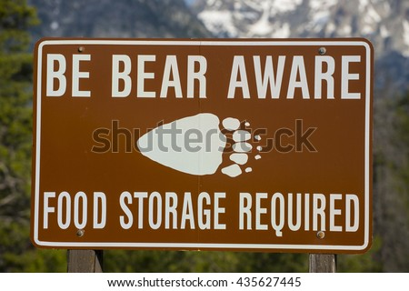 Be Bear Aware warning sign posted in hiking camping area for safety against grizzly attack