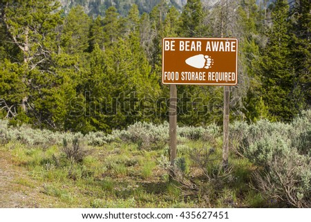 Be Bear Aware warning sign posted in hiking camping area for safety against grizzly attack - stock photo