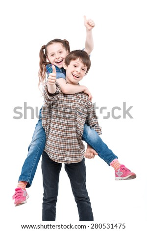 Be my horse. Small handsome boy holding his small pretty sister on his back while both are smiling and showing thumbs up isolated on white background - stock photo